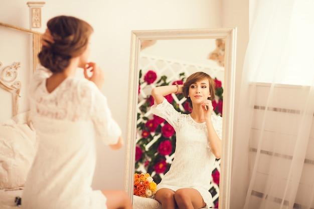 Młoda kobieta, patrząc na siebie w lustrze
