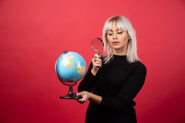 Młoda kobieta, patrząc na świecie z lupą na czerwonym tle
