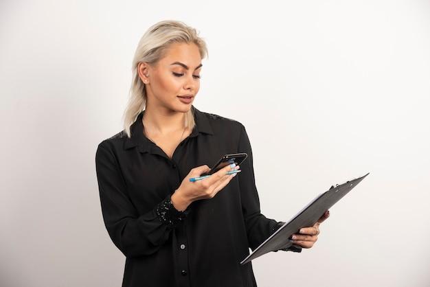 Młoda kobieta, patrząc na telefon komórkowy i trzymając schowek. wysokiej jakości zdjęcie