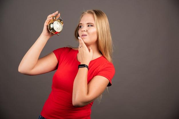 Młoda kobieta patrząc na zegar z wyczerpanym wyrazem twarzy.