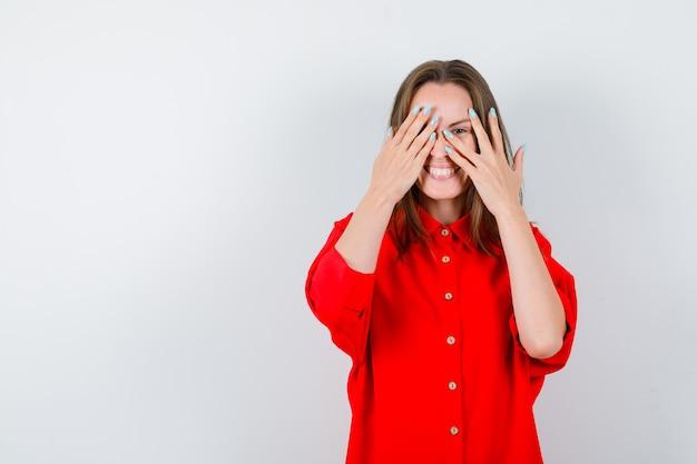 Młoda kobieta patrząc przez palce w czerwonej bluzce i patrząc wesoło, widok z przodu.