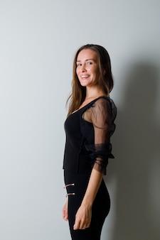Młoda kobieta, patrząc przez ramię i uśmiechnięta z wdziękiem w czarnej bluzce i czarnych spodniach i wyglądająca uroczo