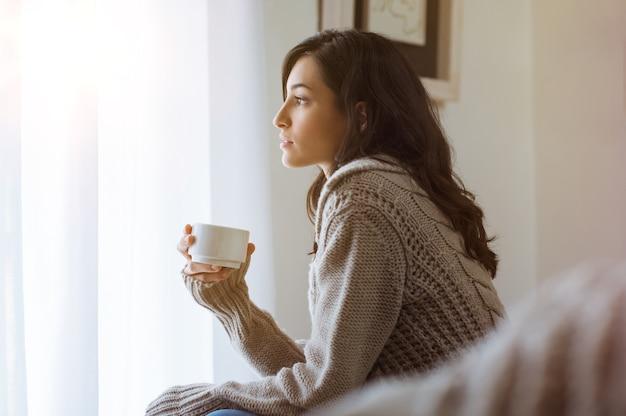 Młoda kobieta, patrząc przez szybę trzyma kawę