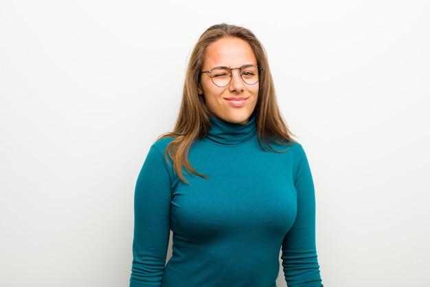 Młoda kobieta, patrząc szczęśliwy i przyjazny, uśmiechając się i mrugając do ciebie z pozytywnym nastawieniem do białej ściany