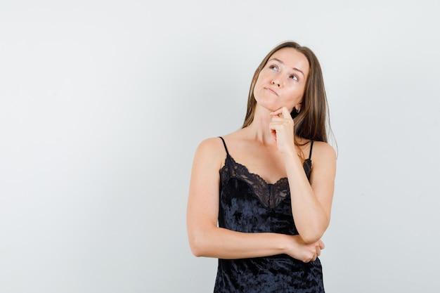 Młoda kobieta, patrząc w czarny podkoszulek i zamyślony.