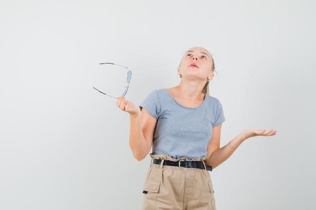 Młoda kobieta patrząc w górę, trzymając okulary, rozkładając dłoń w t-shirt, widok z przodu spodnie.