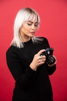 Młoda kobieta patrząc w kamerę na czerwonym tle. wysokiej jakości zdjęcie