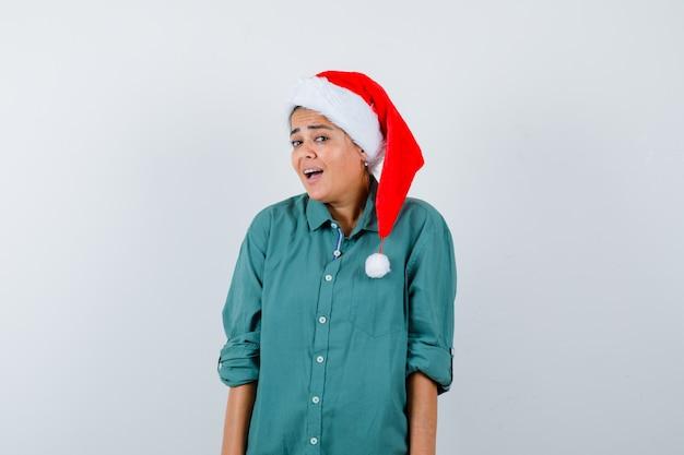 Młoda kobieta patrząc w koszulę, kapelusz santa i patrząc zdziwiony, widok z przodu.