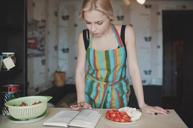 Młoda kobieta, patrząc w książce przepisów