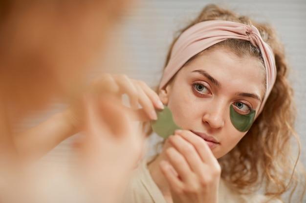 Młoda kobieta patrząc w lustro podczas nakładania plastrów pod oczy