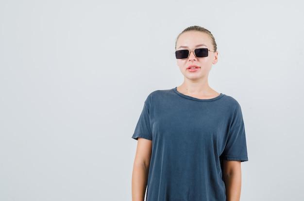 Młoda kobieta, patrząc w szary t-shirt, okulary i wyglądający uroczo