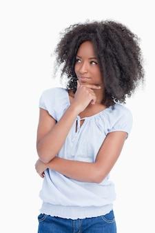 Młoda kobieta, patrząc z boku z rękami skrzyżowanymi i rękę na jej podbródek