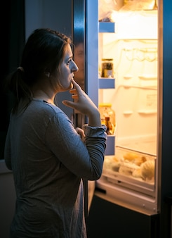 Młoda kobieta patrząca do lodówki późnym wieczorem