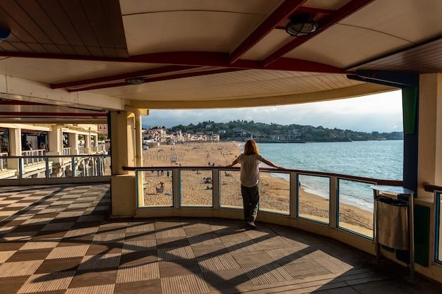 Młoda kobieta patrząca na piękną grande plage w saint jean de luz o zachodzie słońca, wakacje na południu francji, francuski kraj basków