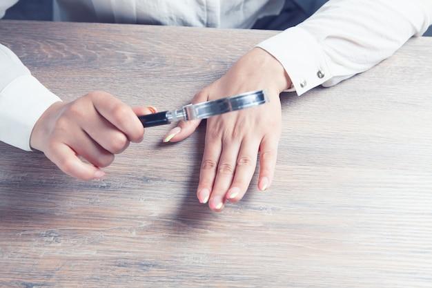 Młoda kobieta patrząca na pomalowane paznokcie ze szkłem powiększającym
