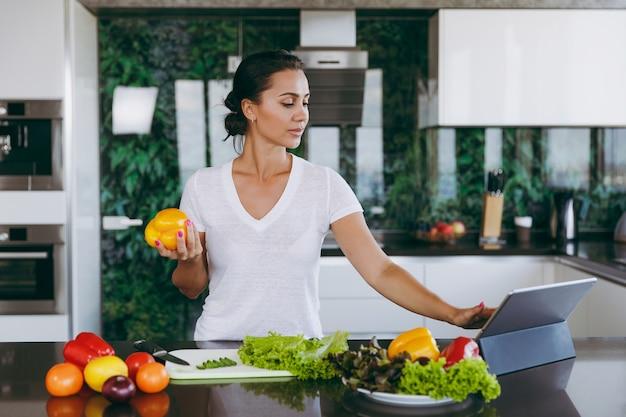 Młoda kobieta patrząca na przepis w laptopie w kuchni