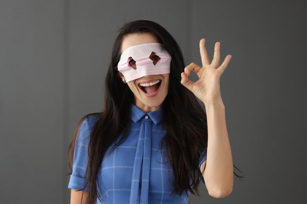 Młoda kobieta patrząca przez dziury w medycznej masce ochronnej i pokazująca ręką ok gest