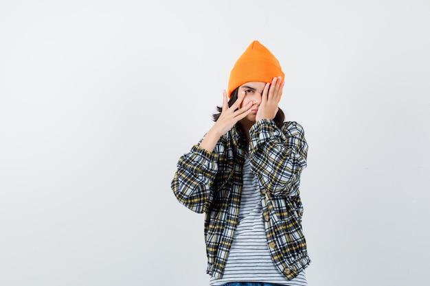 Młoda kobieta patrząca przez palce w pomarańczowym kapeluszu w kratkę, wyglądająca na zaspaną
