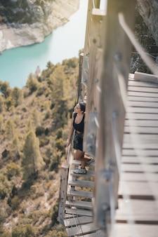 Młoda kobieta patrząca w stronę horyzontu na wiszącej drabinie