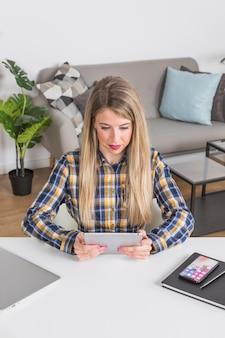 Młoda kobieta patrzeje cyfrową pastylkę przy biurkiem w domowym wnętrzu