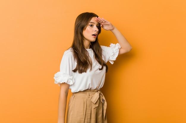 Młoda kobieta patrzeje daleki utrzymuje rękę na czole