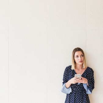 Młoda kobieta patrzeje daleko od z telefonem komórkowym