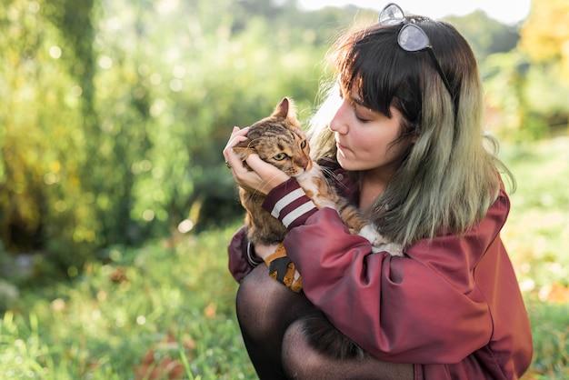 Młoda kobieta patrzeje jej tabby kota w parku