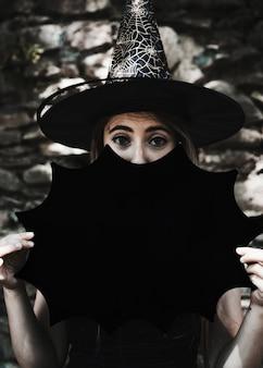 Młoda kobieta patrzeje kamerę w czarownica kapeluszu z halloweenową dekoracją