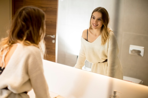 Młoda kobieta patrzeje lustrzanego odbicie w łazience w domu