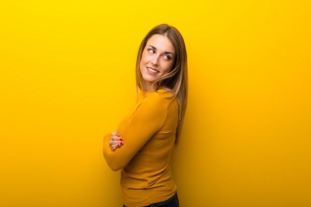 Młoda kobieta patrzeje nad ramieniem z uśmiechem na żółtym tle