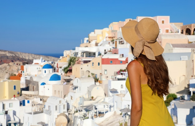 Młoda kobieta patrzy na wioskę oia na wyspie santorini w grecji. słynny kurort greek island jest główną atrakcją turystyczną morza śródziemnego.