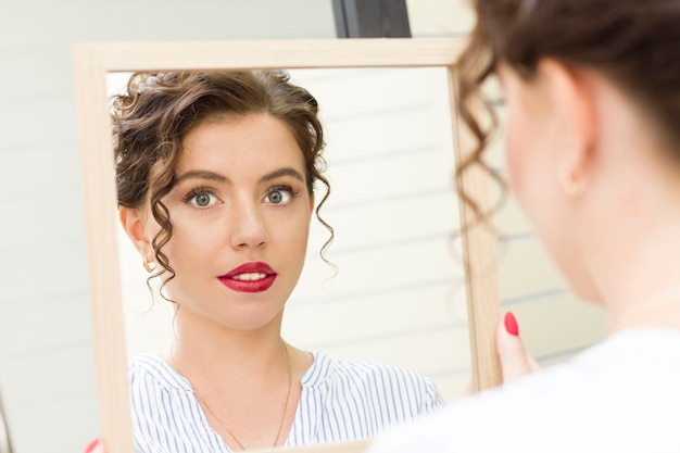 Młoda kobieta patrzy w lustro.