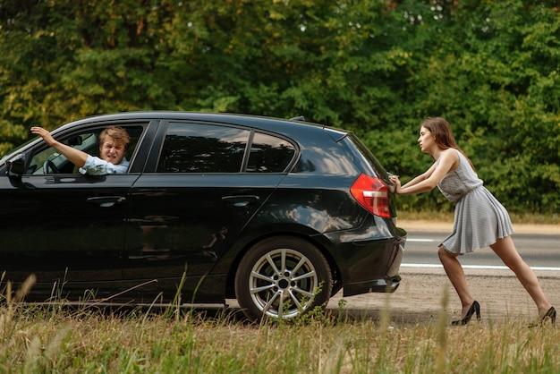 Młoda kobieta pchająca zepsuty samochód z mężczyzną na drodze, awaria