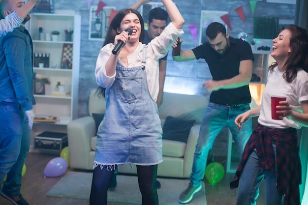 Młoda kobieta pełna radości śpiewa na mikrofonie na imprezie z przyjaciółmi.