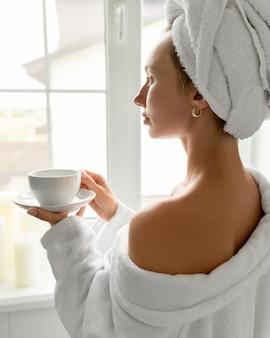 Młoda kobieta pić kawę w łazience. rutyna pielęgnacji skóry. powolne życie przestaje się spieszyć, ciesząc się koncepcją życia