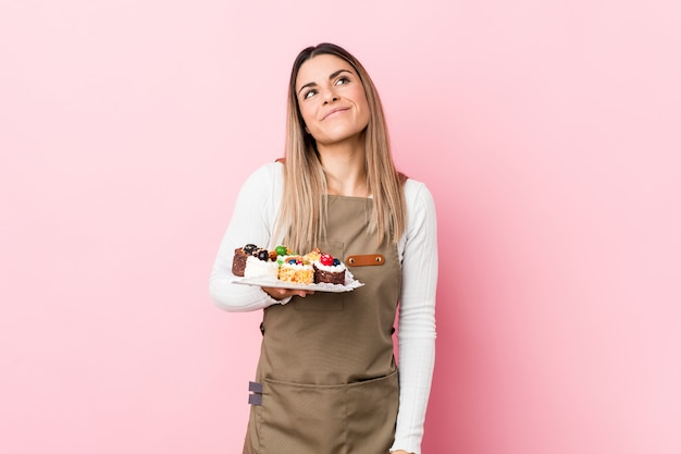 Młoda kobieta piekarz gospodarstwa słodyczy marzy o osiągnięciu celów