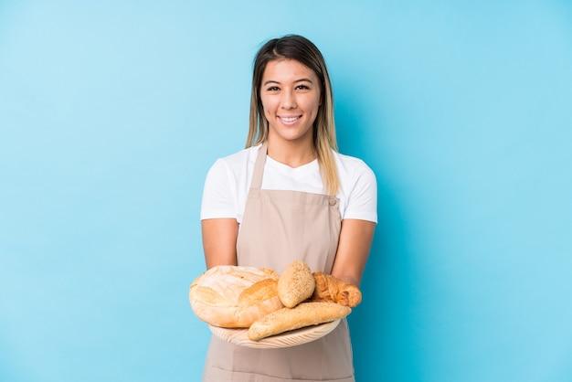 Młoda kobieta piekarz na białym tle szczęśliwy, uśmiechnięty i wesoły