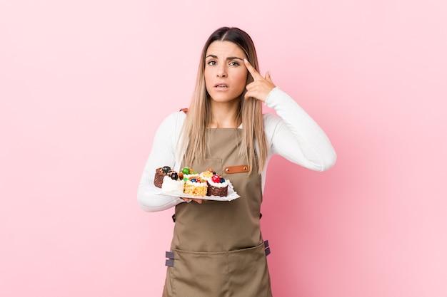 Młoda kobieta piekarz trzyma słodycze pokazując gest rozczarowania palcem wskazującym.