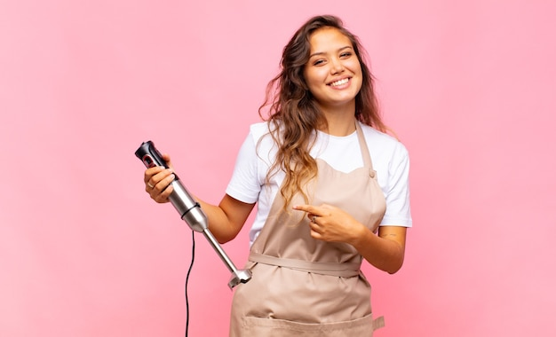 Młoda kobieta piekarz uśmiecha się radośnie, czuje się szczęśliwy i wskazuje na bok i do góry, pokazując obiekt w przestrzeni kopii