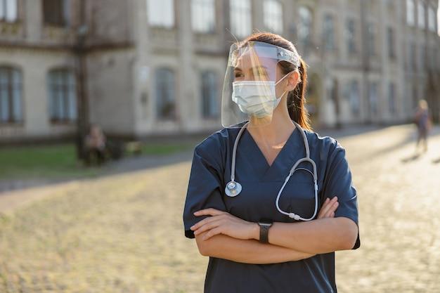 Młoda kobieta pielęgniarka nosząca osłonę twarzy i maskę dla bezpieczeństwa, co jest wymagane, aby zapobiec covid