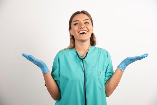 Młoda kobieta pielęgniarka pozowanie z rękami na białym tle.