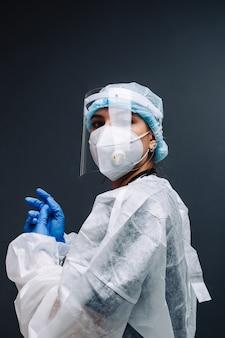 Młoda kobieta pielęgniarka pracownik szpitala w medyczne maski ochronne, rękawiczki i odzież ochronna na białym tle na szarym tle.