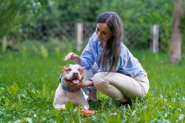 Młoda kobieta pieszczoty amerykański pitbull terrier na trawie w parku szczęśliwy szczeniak z otwartymi ustami