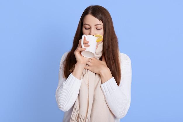 Młoda kobieta pijąca gorącą herbatę, ciemnowłosa kobieta ubrana w biały sweter i szalik, pani dotykająca szyi, z zamkniętymi oczami, pozująca odizolowana na niebieskiej ścianie.