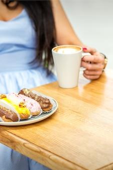 Młoda kobieta pijąca kawę ze słodkimi apetycznymi eklerami siedząca przy stole w kawiarni