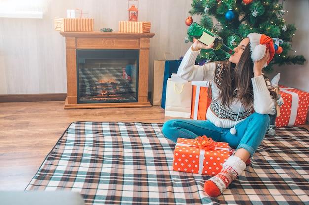 Młoda kobieta pije alkohol z zielonej butelki. siedzi na podłodze i trzyma głowę ręką.