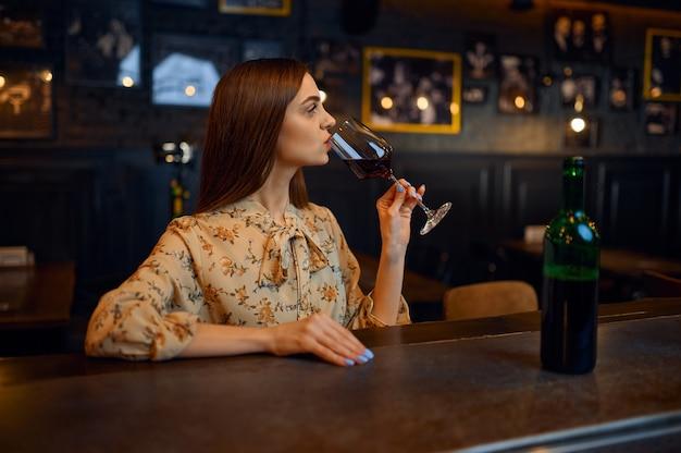 Młoda kobieta pije czerwone wino przy kasie w barze