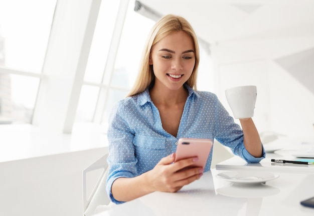 Młoda kobieta pije filiżankę herbaty, sprawdzając telefon komórkowy