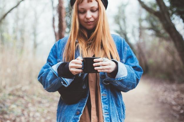 Młoda kobieta pije filiżankę kawy na brzegu jeziora