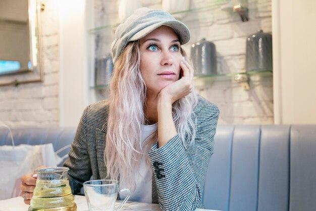 Młoda kobieta pije herbatę w kawiarni. piękna blondynka w czapce zastanawiała się wyglądając przez okno.